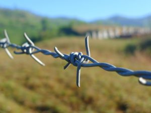 Picture of barbed wire up close with grassland, hills and blue sky out of focus in the background.