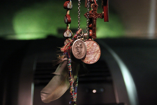A medallion depicting Saint Christopher – the patron saint of travellers – hangs from the rear view mirror of a car.